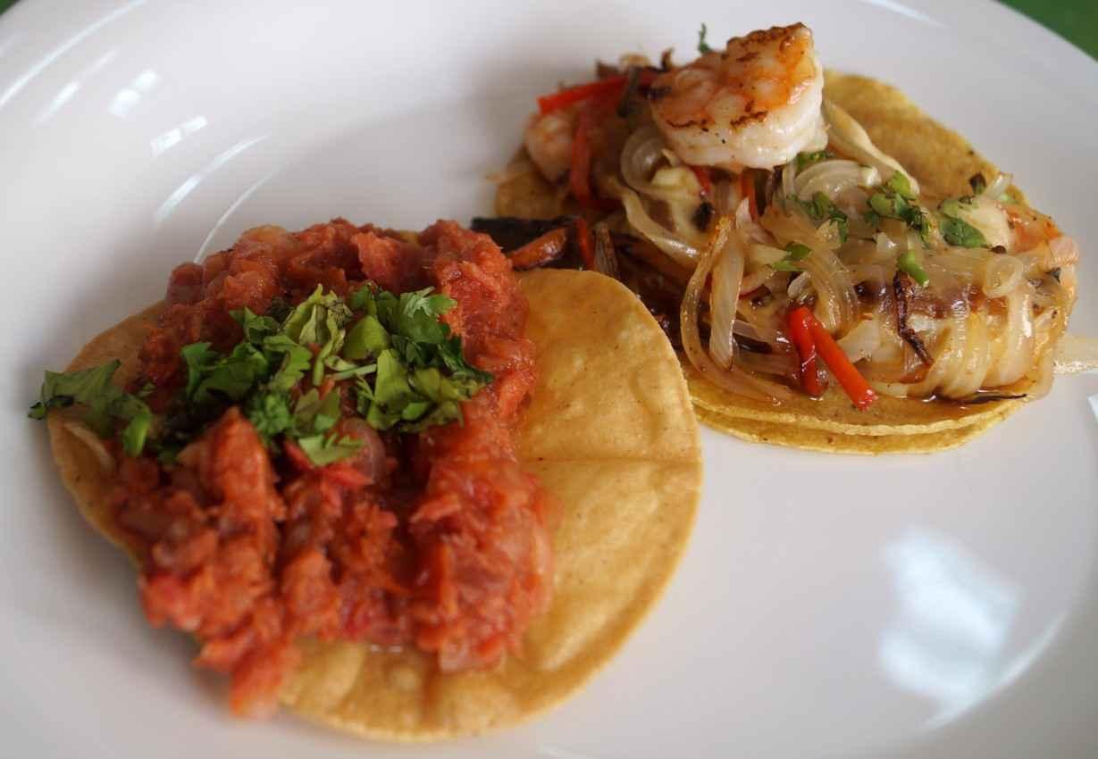 Several seafood and pork soft tacos.