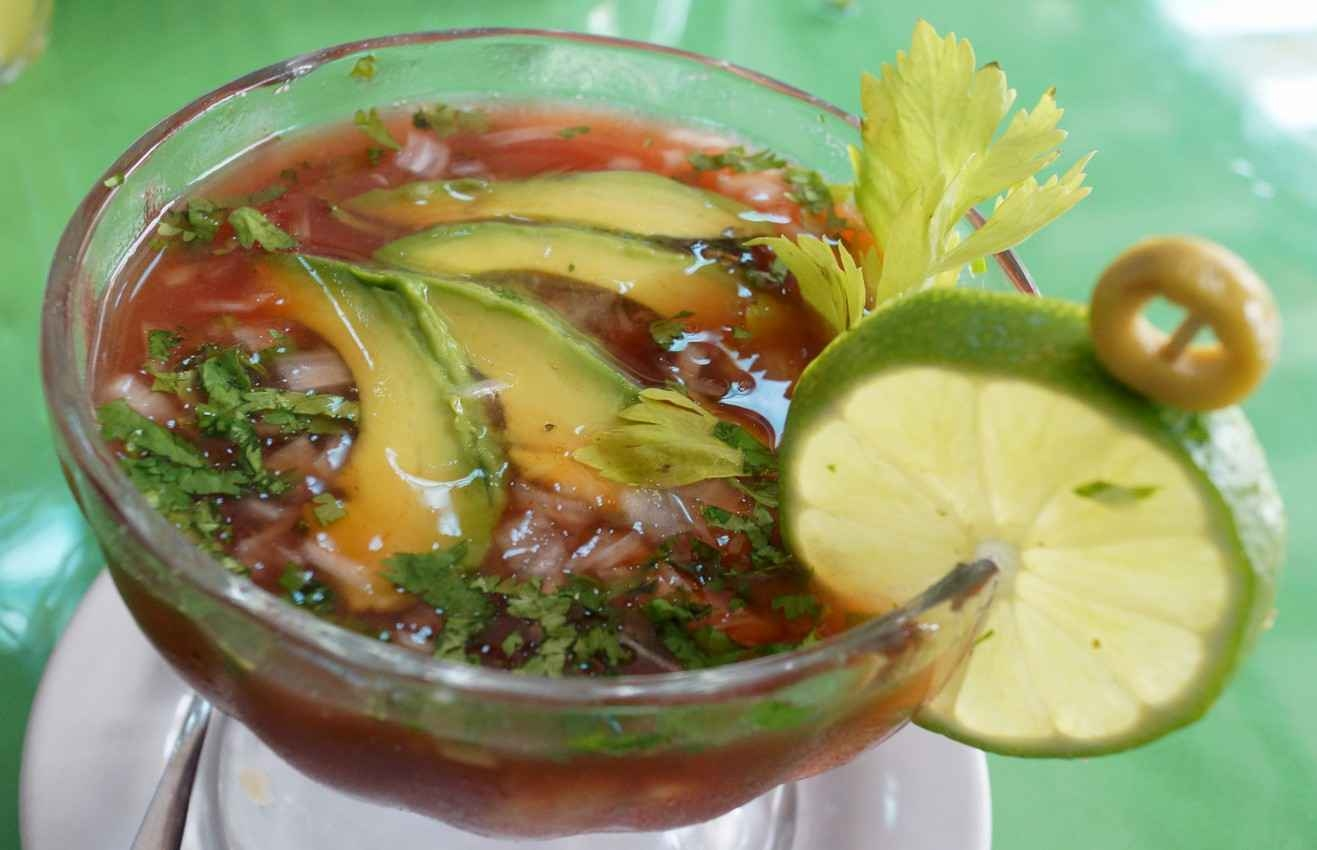 A seafood cocktail served in a large glass with avocado and lime slices.