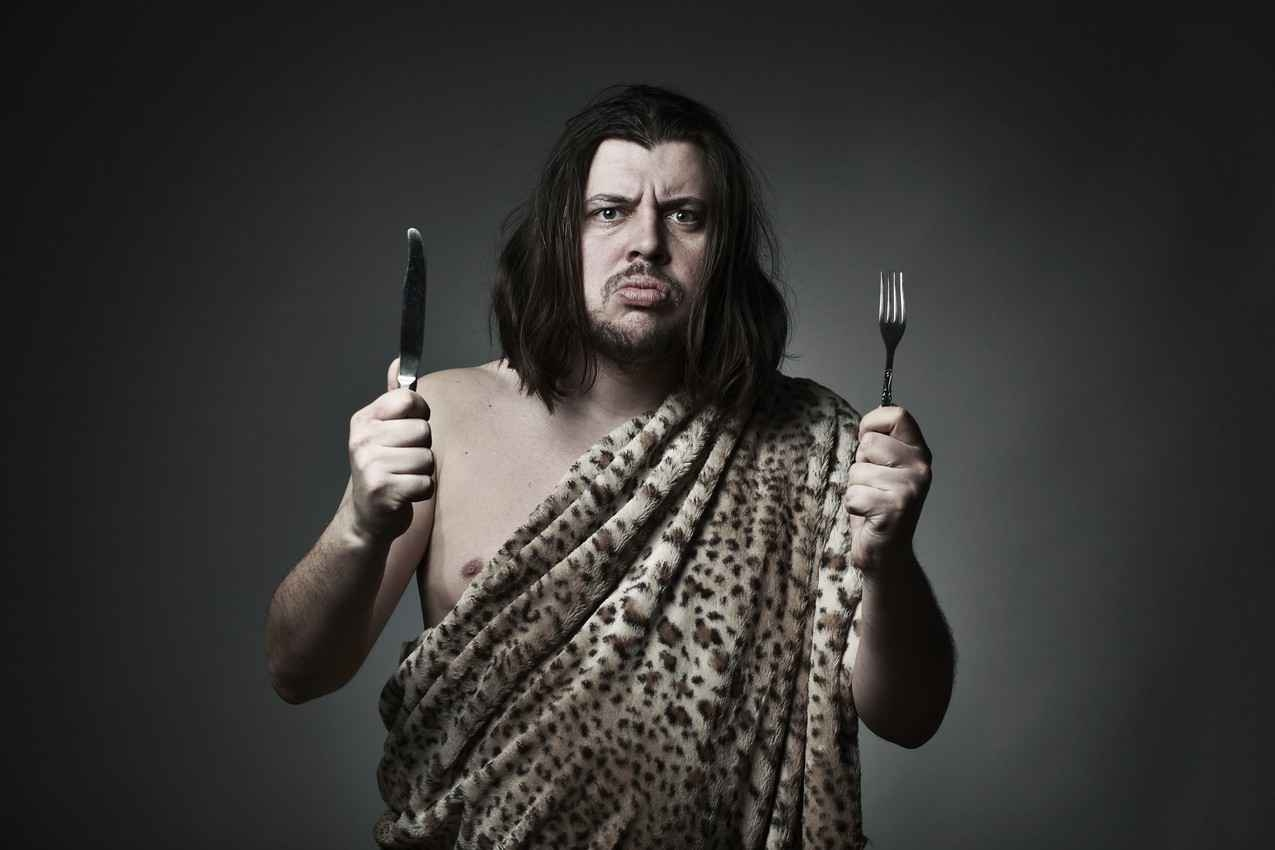 A caveman holding a knife and a fork.