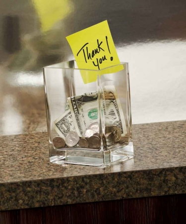 A tip cup with money in it and a thank you note.
