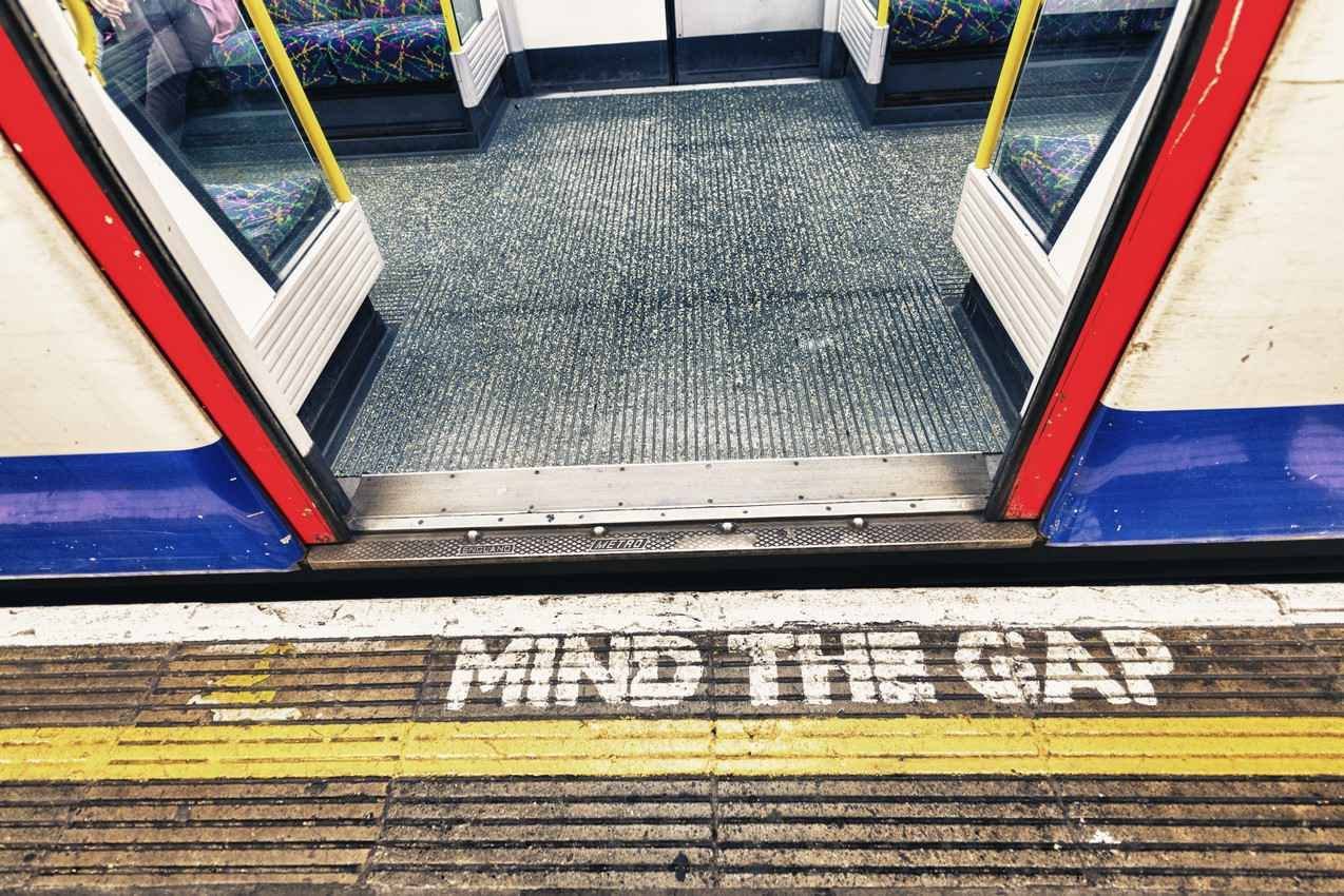 Mind the gap written on the walkway near a subway entrance.
