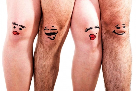 A man's and woman's legs with faces painted on them.