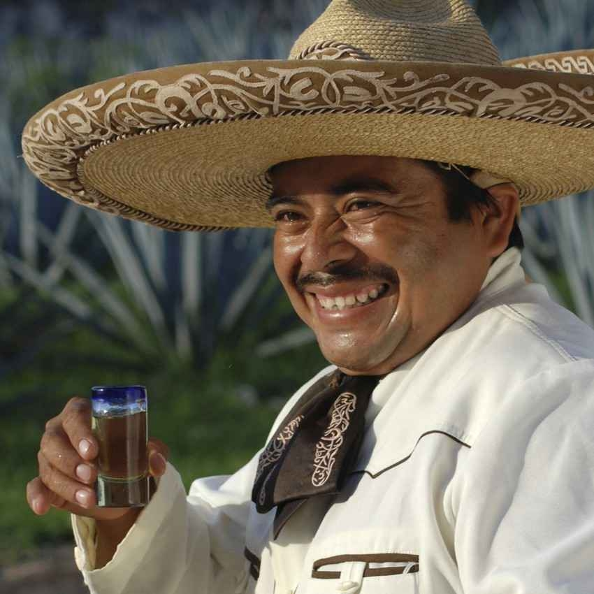 A Mexican bozo taking a shot of tequila.