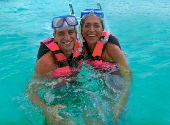 A man and a woman are smiling while they are snorkeling at Xcaret themepark.