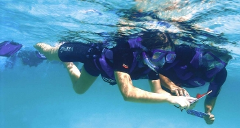 Several people are snorkeling and using underwater maps to guide them.