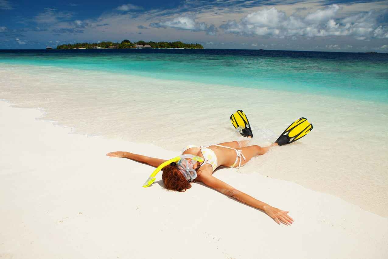 A woman with big boobs, a snorkeling mask, and fins is lying on the beach near Cozumel Island.
