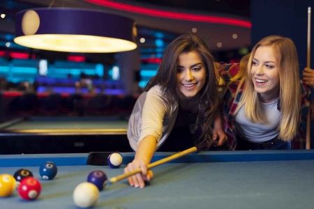 Two extremely sexy women playing pool at a swanky bar.