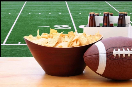 A football game playing in the background with tortilla chips and beer.