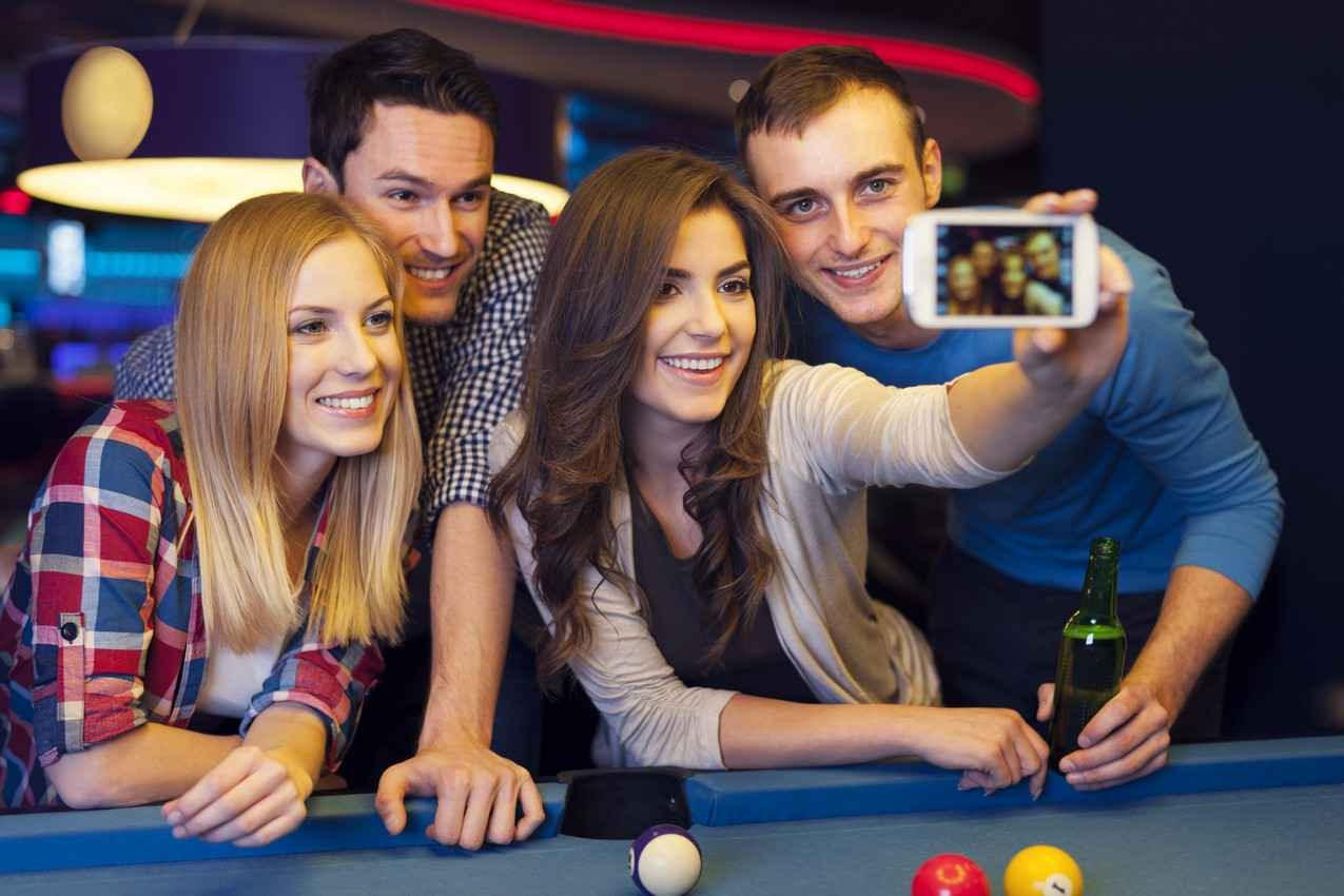 Two men and two women taking selfies at a sports bar.