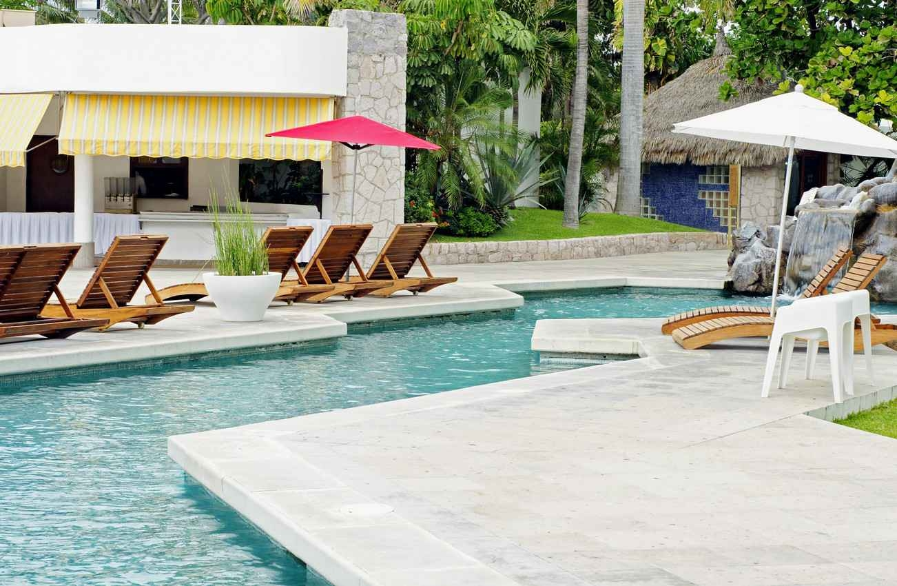 An example of a luxurious piece of property featuring a swimming pool with a waterfall and lounge chairs.