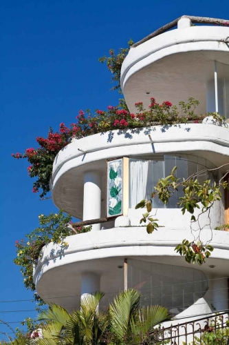 A timeshare for sale with many flowers and round balconies.