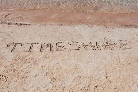 The word TIMESHARE written in sand on a Mexican beach.