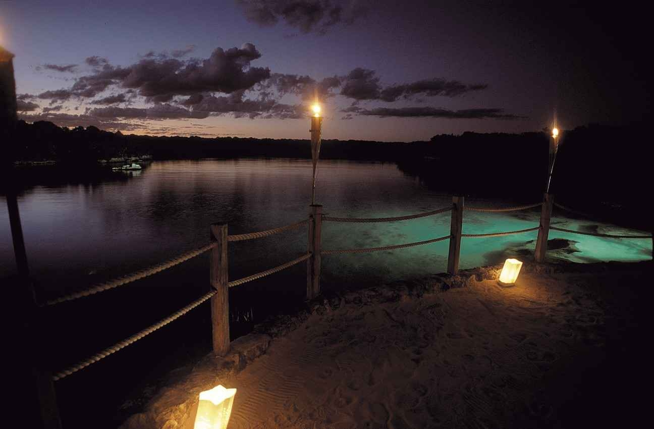 A candlelit walkway near the Cozumel coastline.