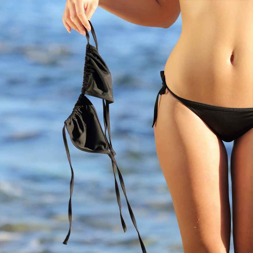 A topless woman holding her bikini top at her side.