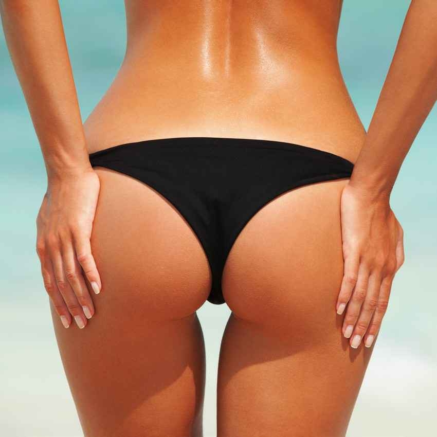 A topless woman showing off her butt in a black bikini.