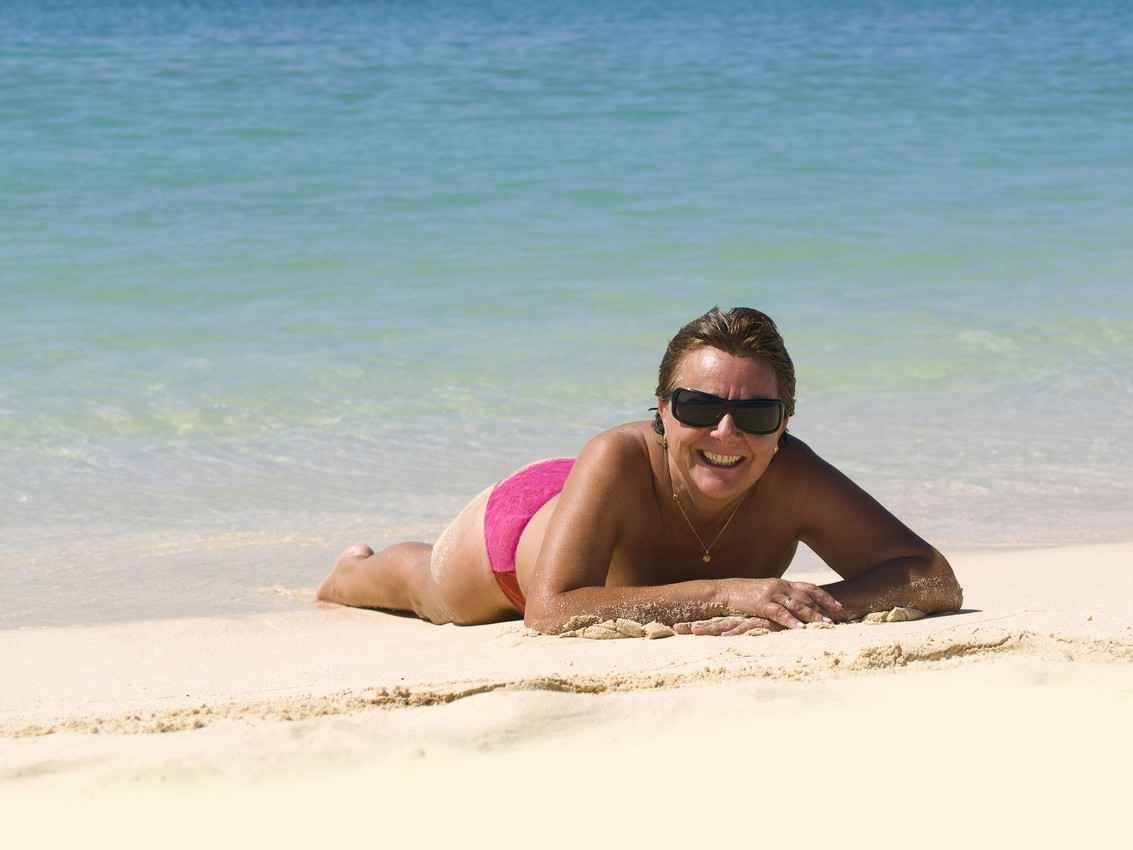 A topless woman lying facedown on a beach in Playa Del Carmen.