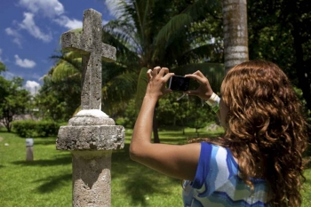 A woman taking a close-up photograph of a Christian cross at a Mexican cemetery.