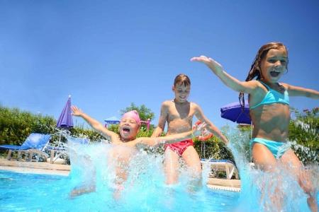 Three children playing at a swimming pool in Playa Del Carmen.
