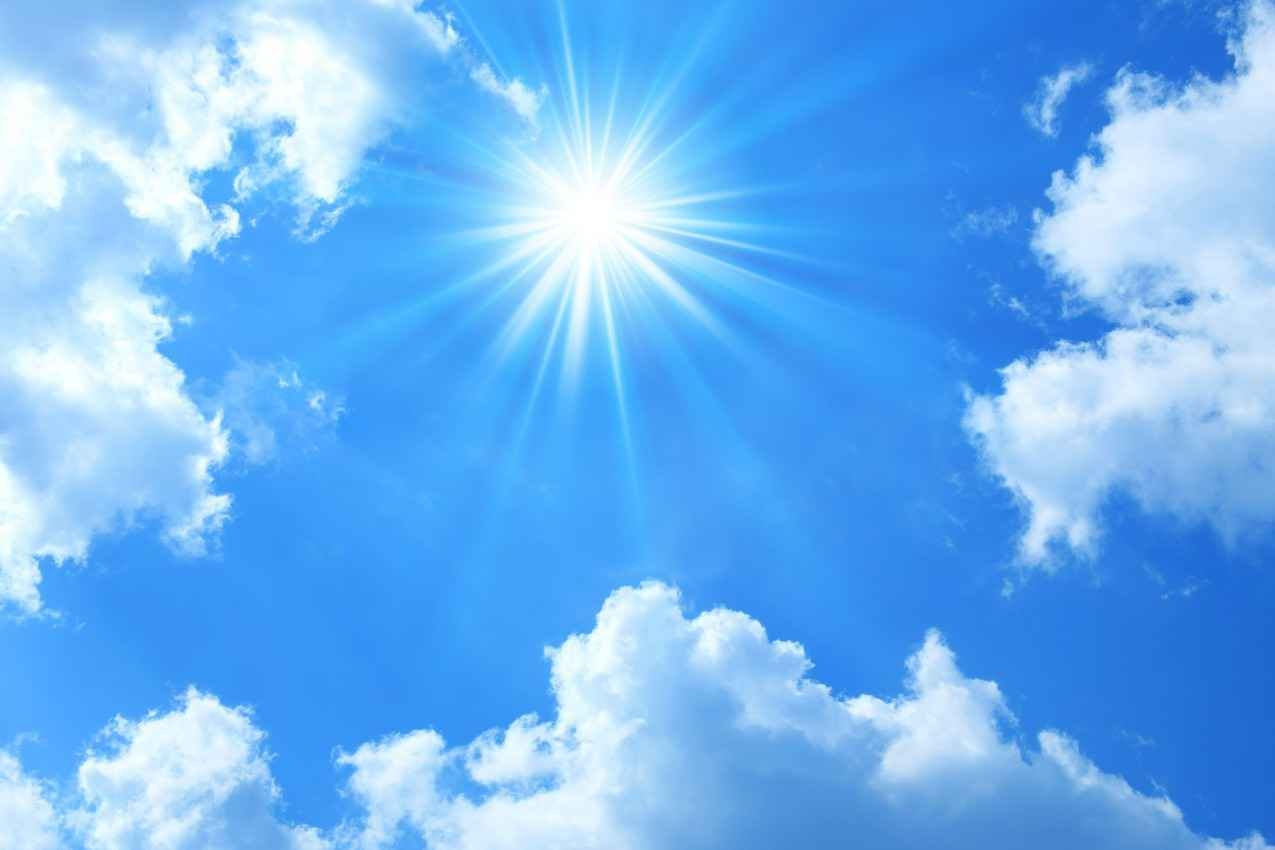 The sun shining with light clouds and a blue sky.