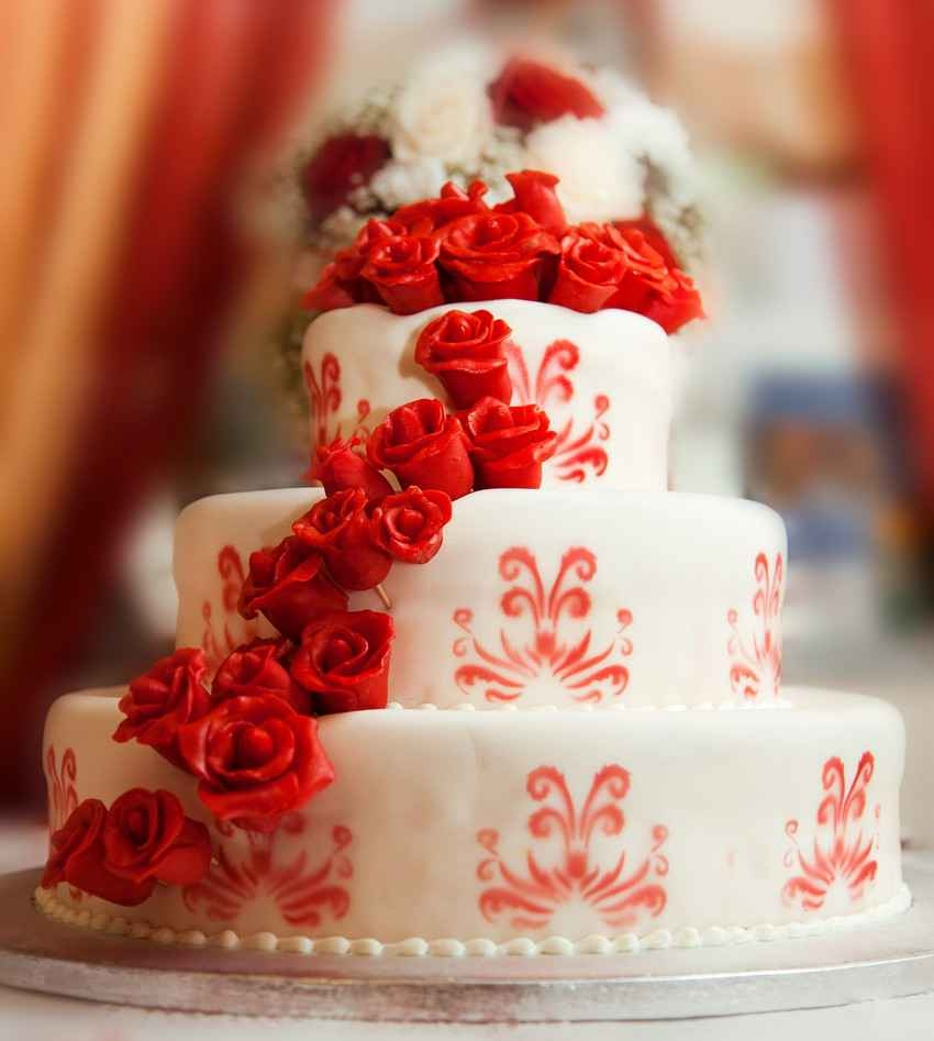 An amazing wedding cake with candy roses all over it.