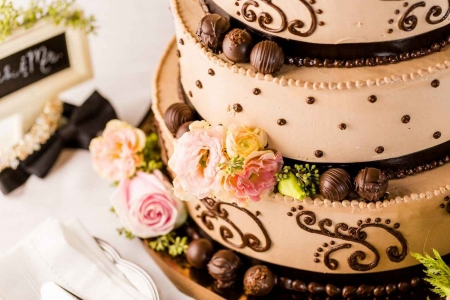 A vanilla wedding cake covered with chocolates.