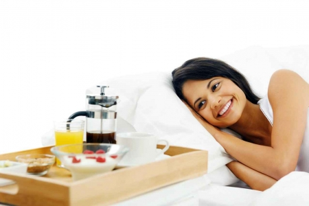 A woman smiling after receding breakfast in bed as part of a wedding package in Playa Del Carmen.