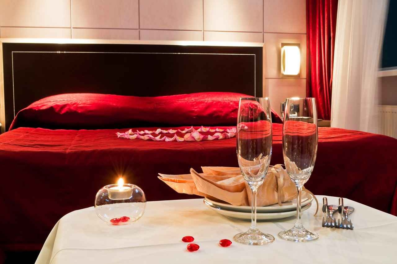 A sexy and romantic resort bed with heart flower petals and several champagne glasses.