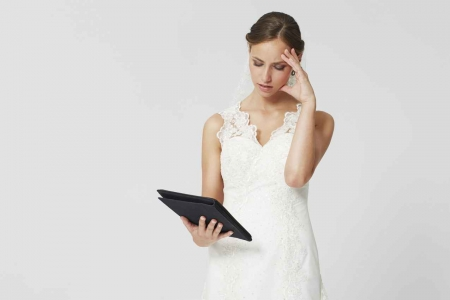 A woman in a bridesmaid dress looking at a notebook of wedding tasks to do.