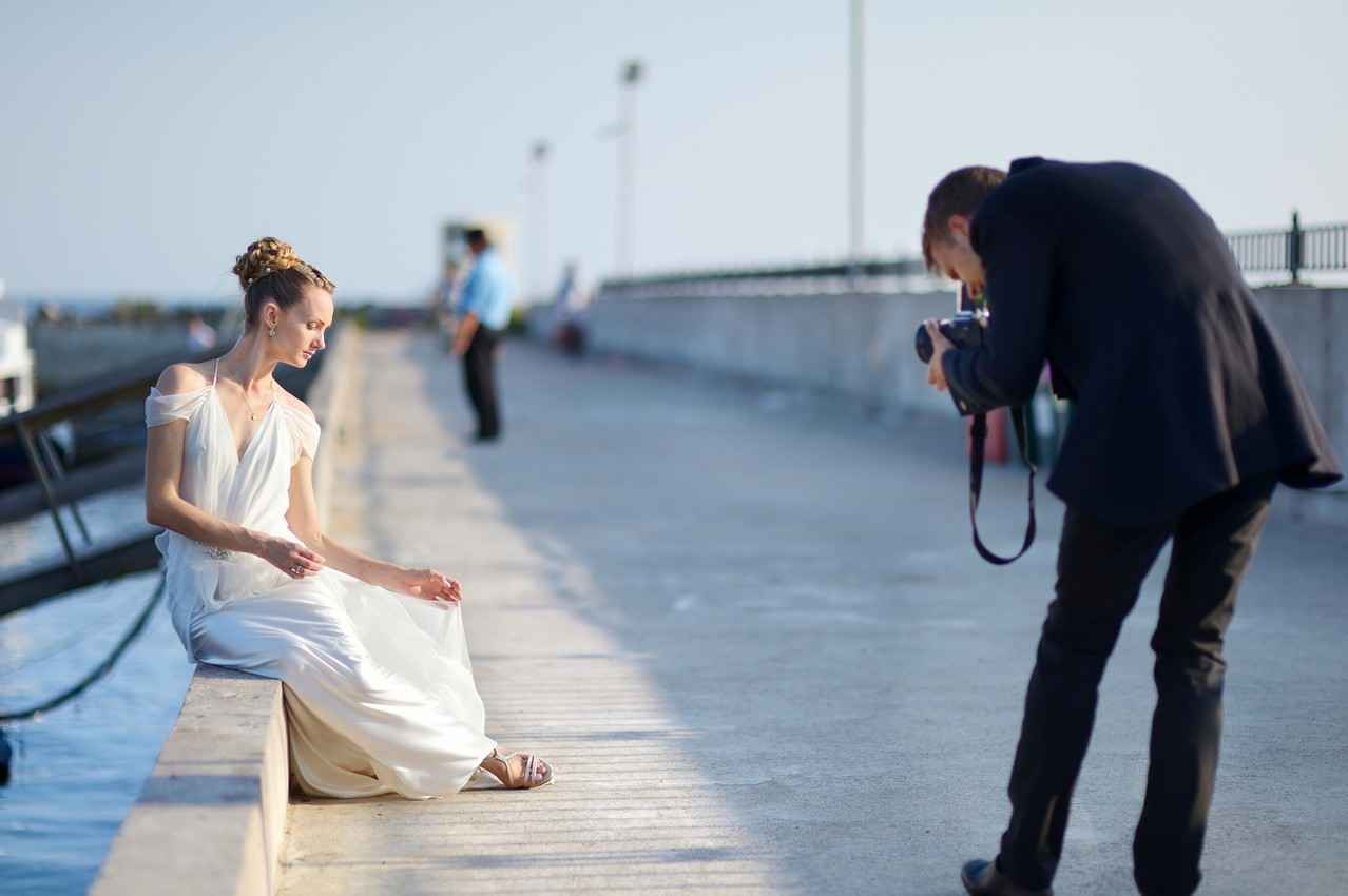 A photographer taking shots of the bride on one of the piers in Playa Del Carmen.
