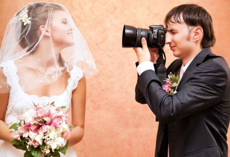 A groom taking a picture of a bride before their wedding ceremony.