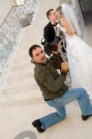 A wedding photographer taking a picture of a married couple on a large staircase.