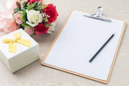 A clipboard with a black pencil, wedding present, and a bouquet.