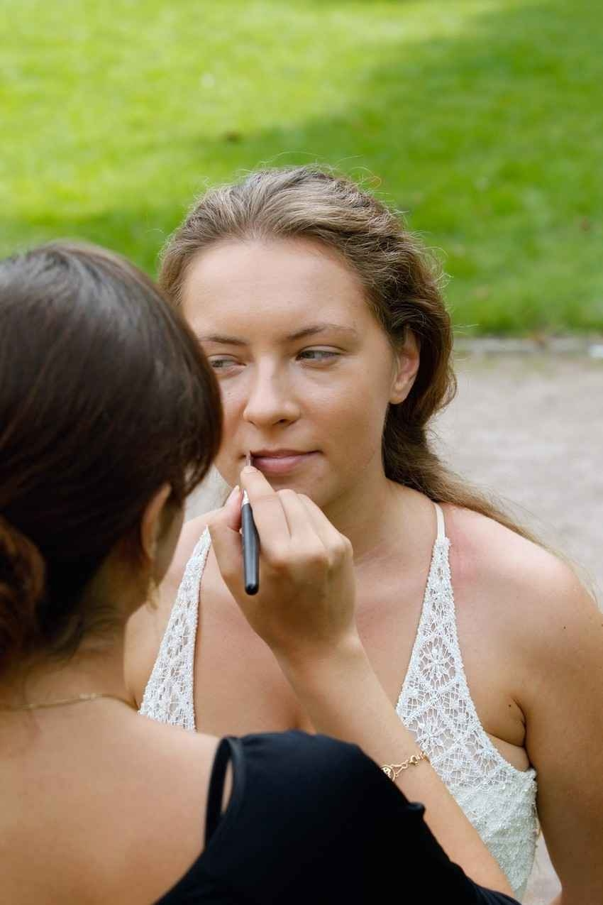 A woman helping a bridesmaid put on lipstick.
