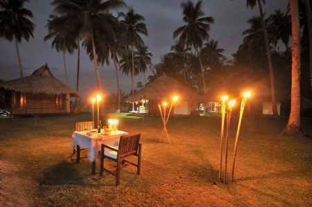 A romantic candlelit dinner with a table and tiki torches.