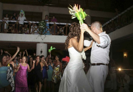 Two recently married couples dancing at a Playa Del Carmen wedding hall.