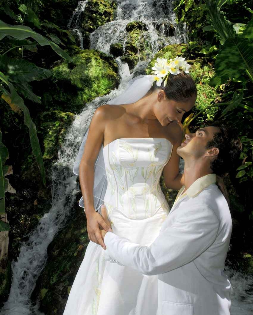 A bride and groom photo taken in the jungle near a beautiful waterfall.
