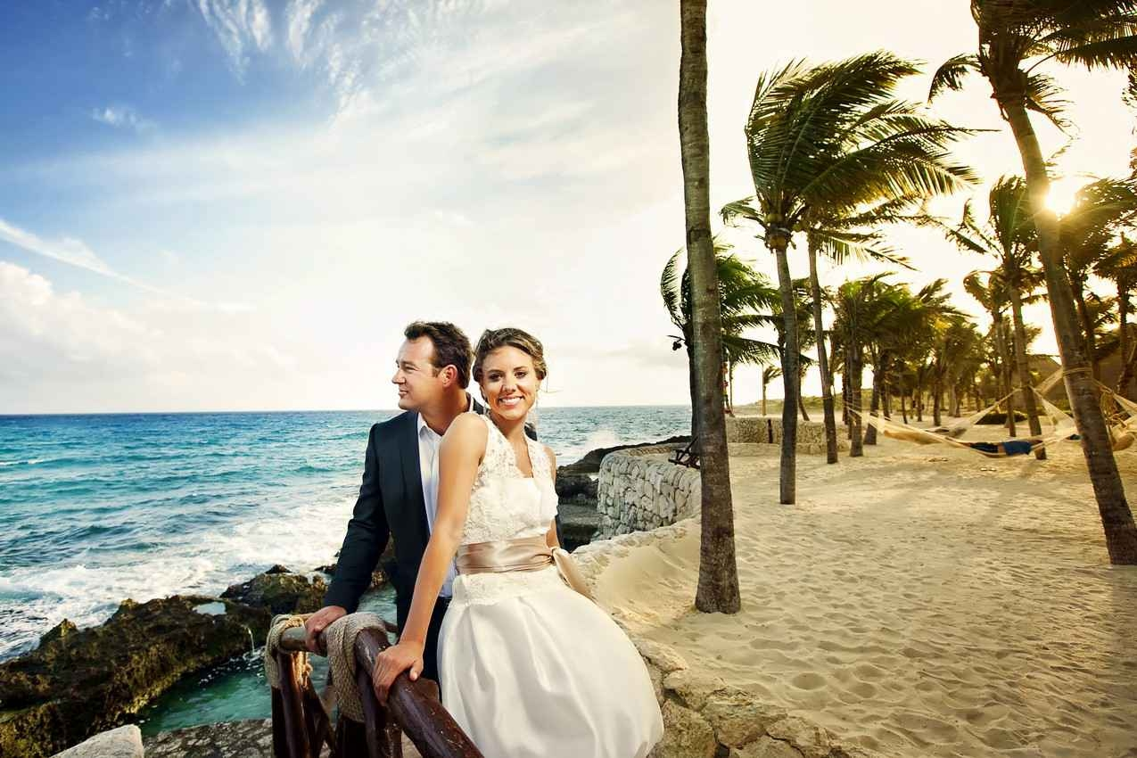 A recently married man and woman standing near the beach with palm trees and hammocks behind them.