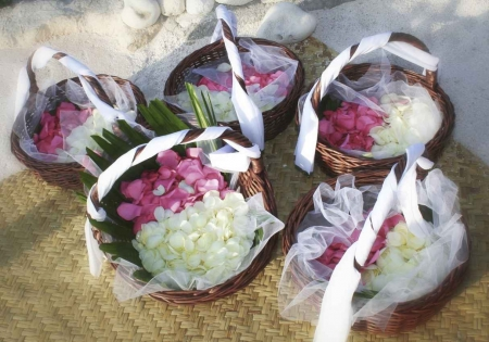 Several flower petal baskets ready for a beach wedding.