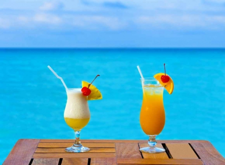 Two cocktails on a table overlooking the Caribbean Sea.