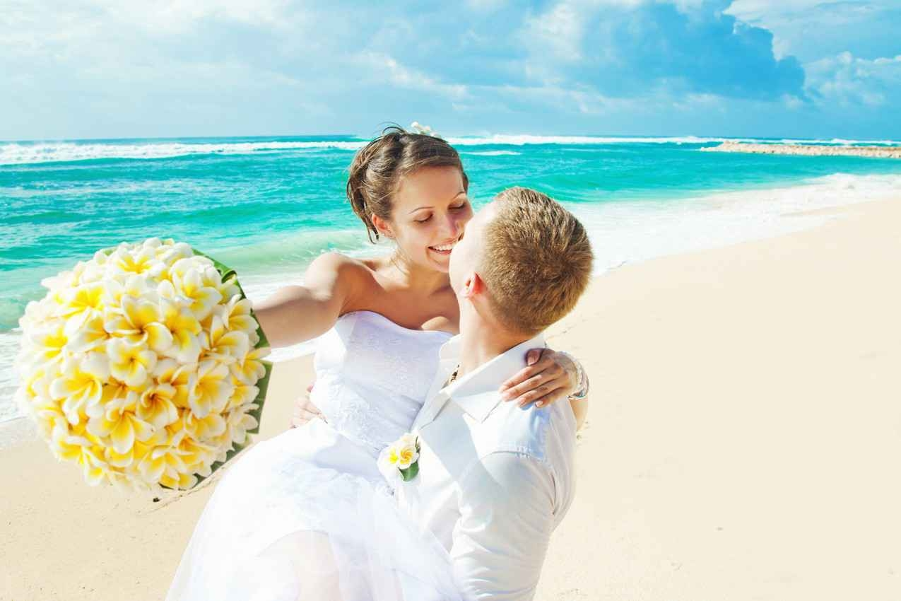 A wedding couple on the beach with the woman holding a bouquet.