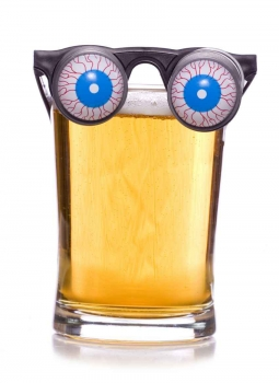 Plastic beer goggles on a glass of beer.