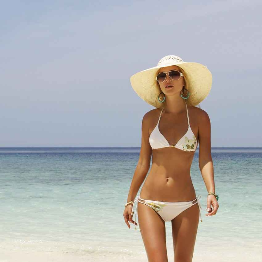 A super hot blonde walking along the beach with a large sun hat on her head.
