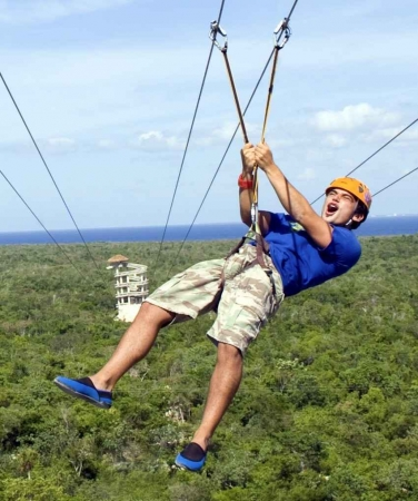 A person wearing an orange helmet riding a zip line.