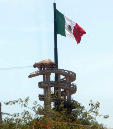 A zip line tower with the Mexican flag waving on the top.
