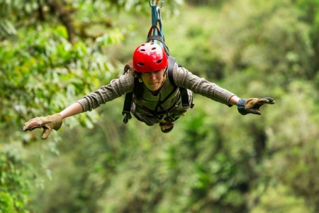 A woman with a red helmet riding a zip line in the jungle.