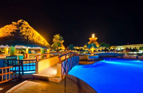 A swimming pool at night with many lights in an all-inclusive resort.