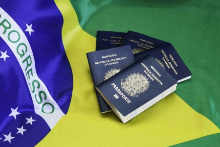 Several Brazilian passports on top of a Brazilian flag.