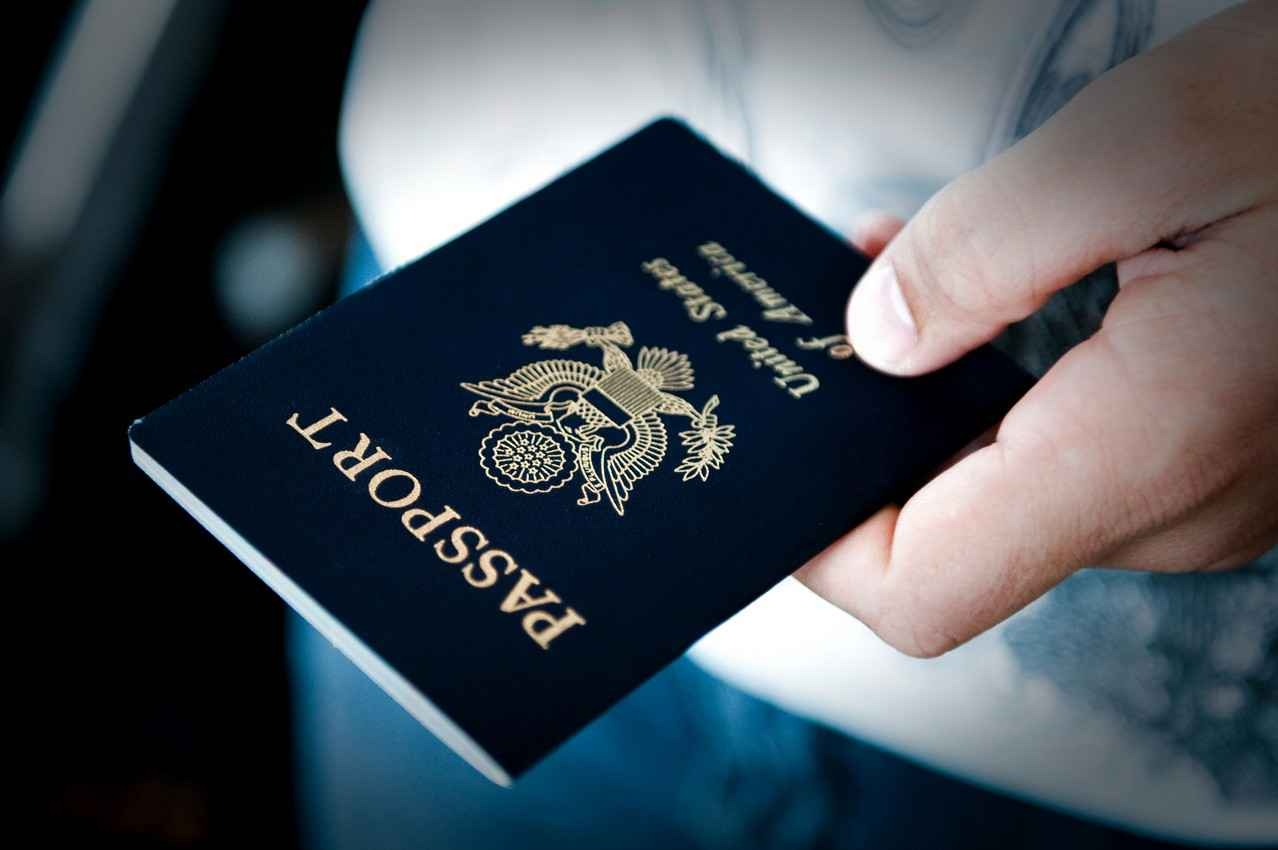 A fat man holding a United States passport.
