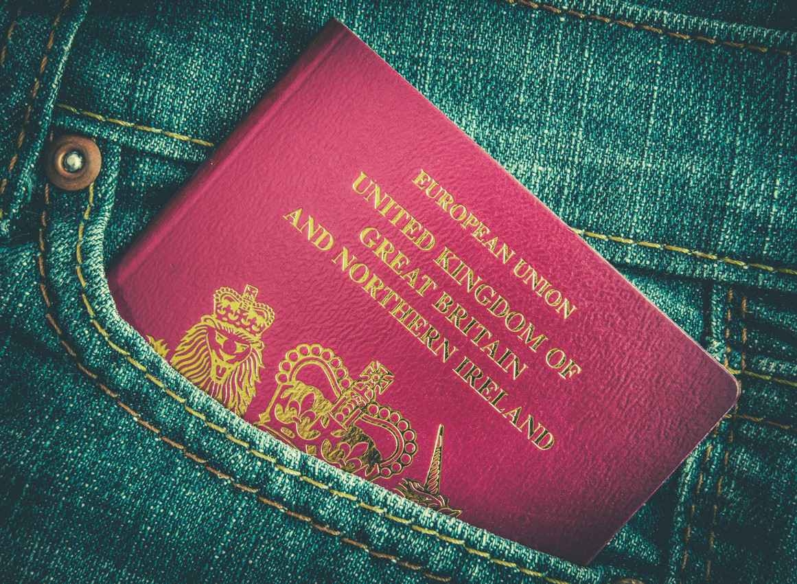 A United Kingdom passport in the back pocket of someone's jeans.