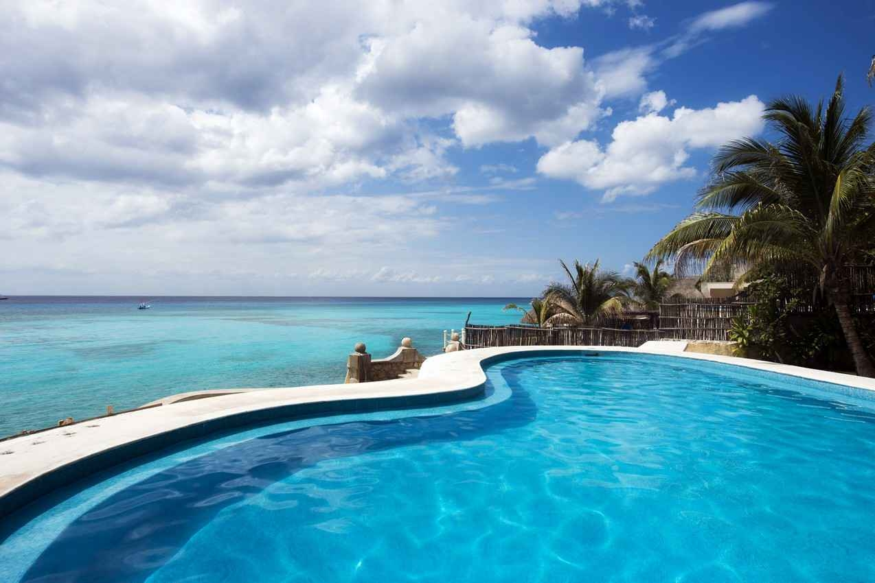 A swimming pool overlooking the beach at a Playa Del Carmen villa.